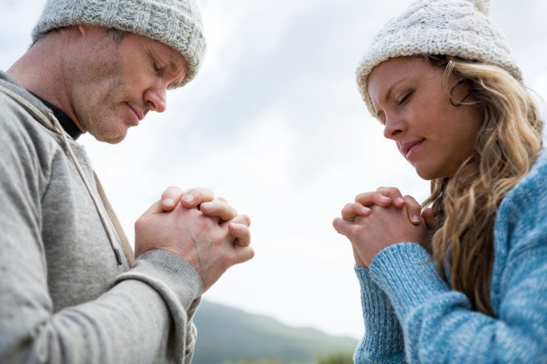 Couple praying with hands clasped on beach